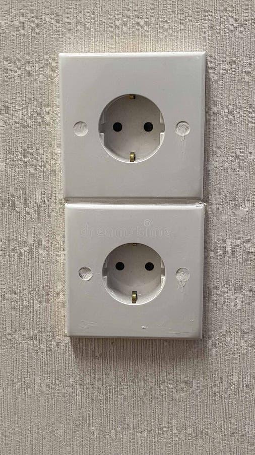 Installera vitt elektriskt uttag på väggen royaltyfria foton