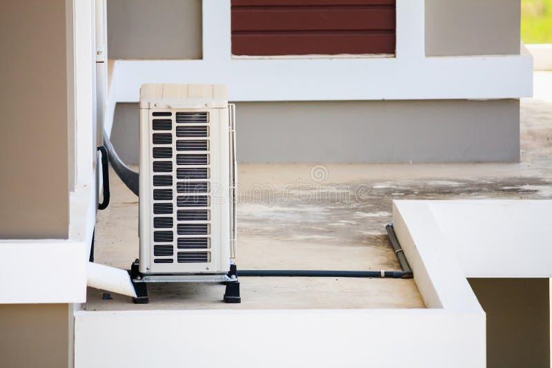 Installerar den utomhus- enheten för luftvillkoret utanför huset royaltyfria bilder