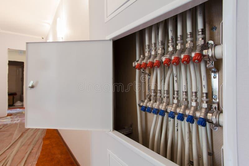 Installeras vita plast-rör för rörmokeri, monteringar och bollventiler i lägenhet under constraction royaltyfri fotografi