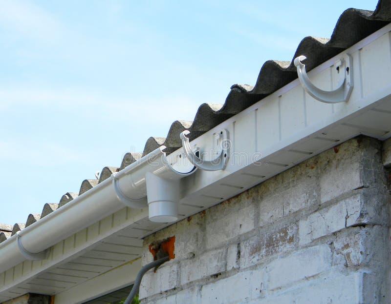 Installerend de plastic houder van de dakgoot voor dowspoutrioolbuis openlucht Het plastic dak guttering, regen het guttering royalty-vrije stock fotografie