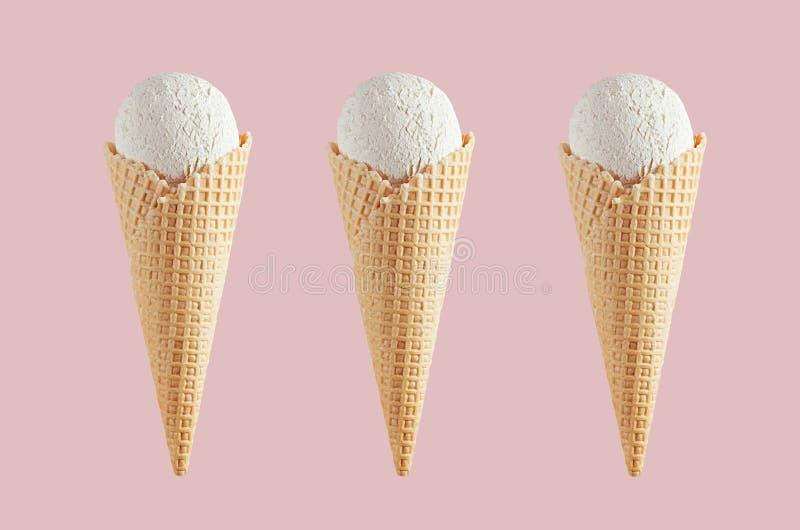 Installi del gelato cremoso bianco tre nei coni croccanti della cialda sul fondo rosa pastello della luce morbida, falso per prog fotografie stock