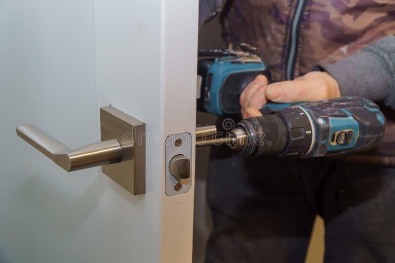 Installi la maniglia di porta con una serratura, carpentiere stringono la vite, facendo uso di un cacciavite del trapano elettric fotografia stock