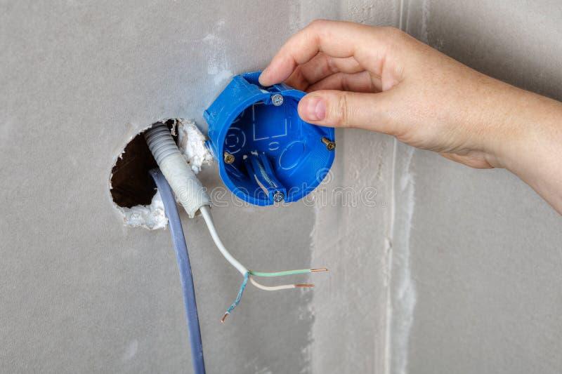 Installieren Sie elektrischen Kasten in das Wandloch, Handnahaufnahme lizenzfreies stockbild