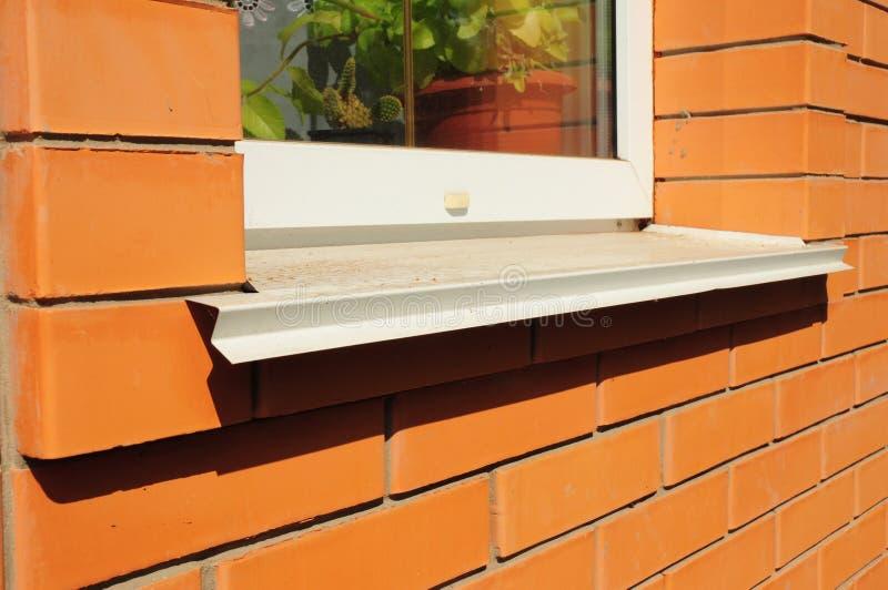 Installieren Sie Weißmetallfensterbrett auf das Backsteinhaus lizenzfreie stockfotografie