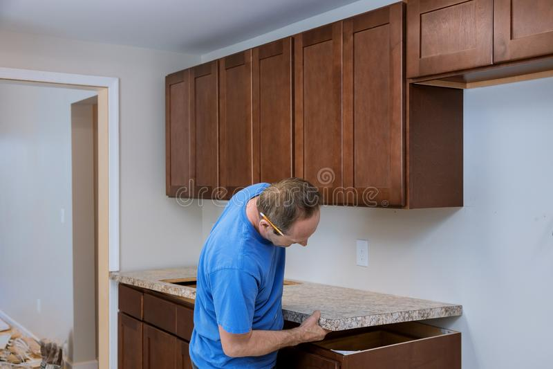 Installierung Auftragnehmer eine lamellenförmig angeordnete Gegenspitze, die eine Küche umgestalten stockfotografie
