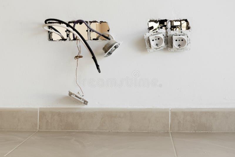 Installierung von elektrischen Sockeln auf eine Wand stockfotografie