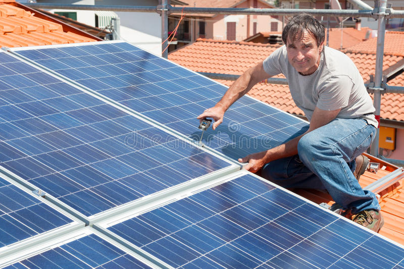 Installing alternative energy photovoltaic solar panels royalty free stock image