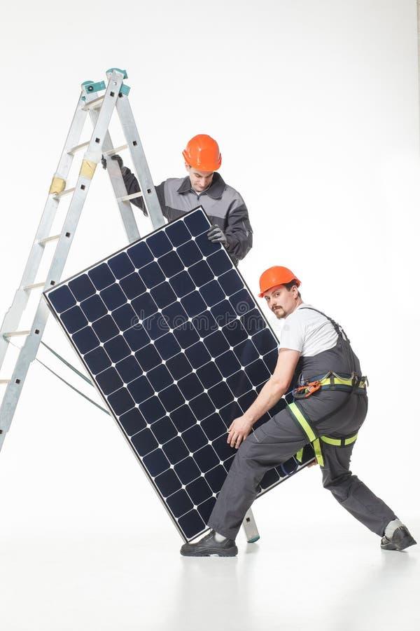 Installing alternative energy photovoltaic solar panels stock photography