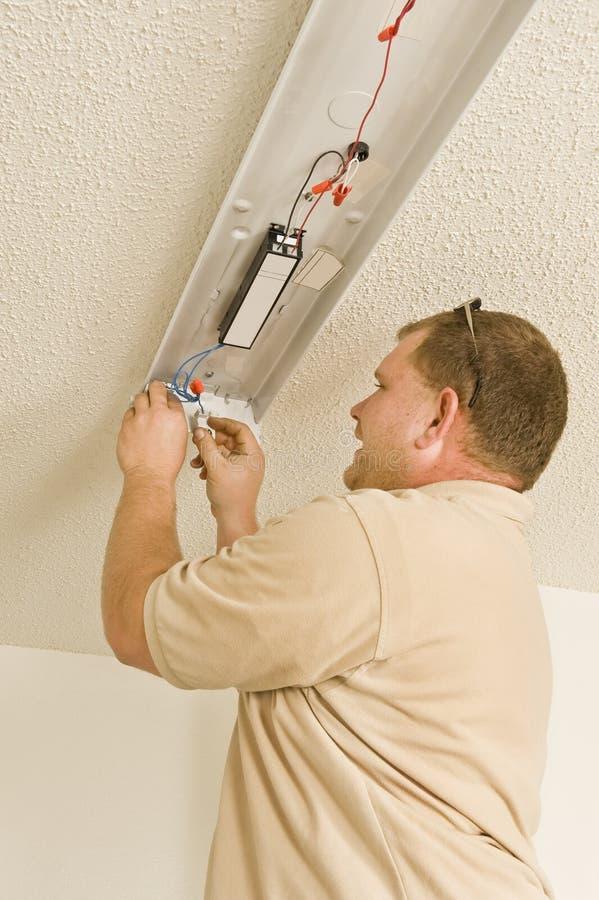 Installing Ballast In Fluorescent Light Fixture. A maintenance man installs the ballast in a fluorescent light fixture in an apartment stock image