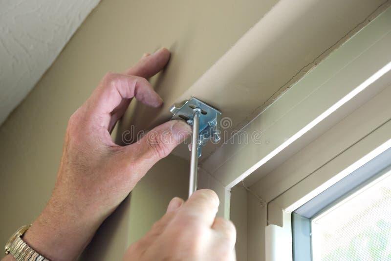 Installing Blinds. Hands installing blind hardware onto window frame stock images