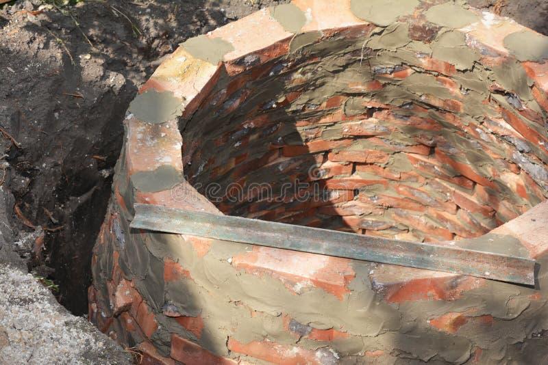 Installing brick septic tank. Sewer brick tank hole installation on house construction site. Photo royalty free stock photos
