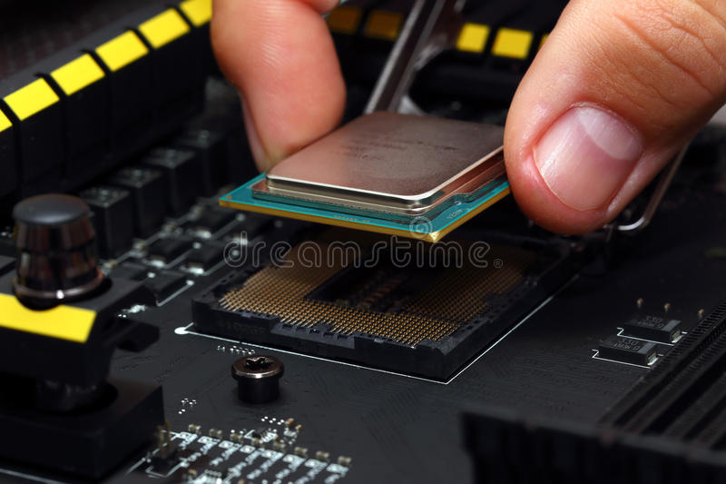 Installing central processor unit into motherboard. Installing modern central processor unit into motherboard stock images