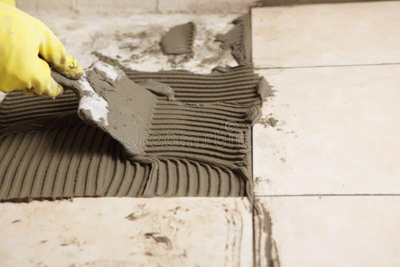Installing ceramic tiles on a floor stock photo
