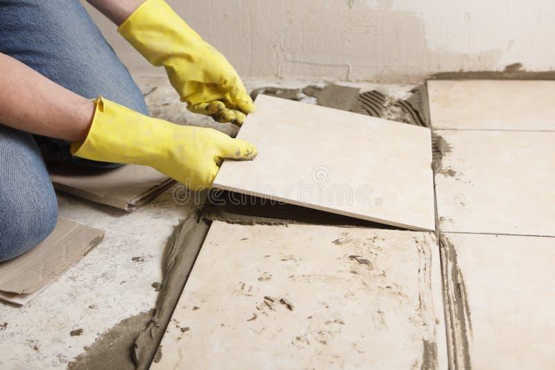 Installing ceramic tiles on a floor. Tiler installing ceramic tiles on a floor stock photo