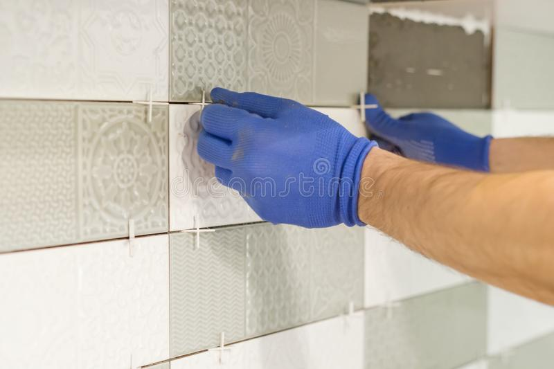Installing ceramic tiles on the wall in kitchen. Placing tile spacers with hands, renovation, repair, construction royalty free stock image