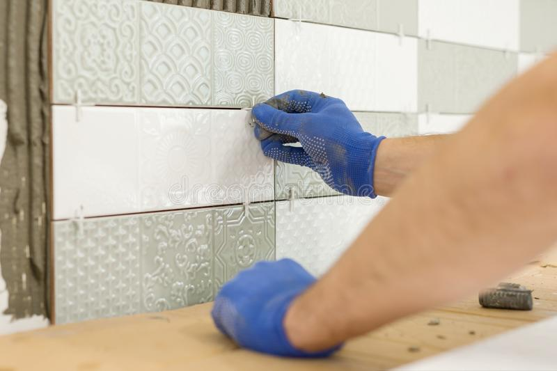 Installing ceramic tiles on the wall in kitchen. Placing tile spacers with hands, renovation, repair, construction stock photos