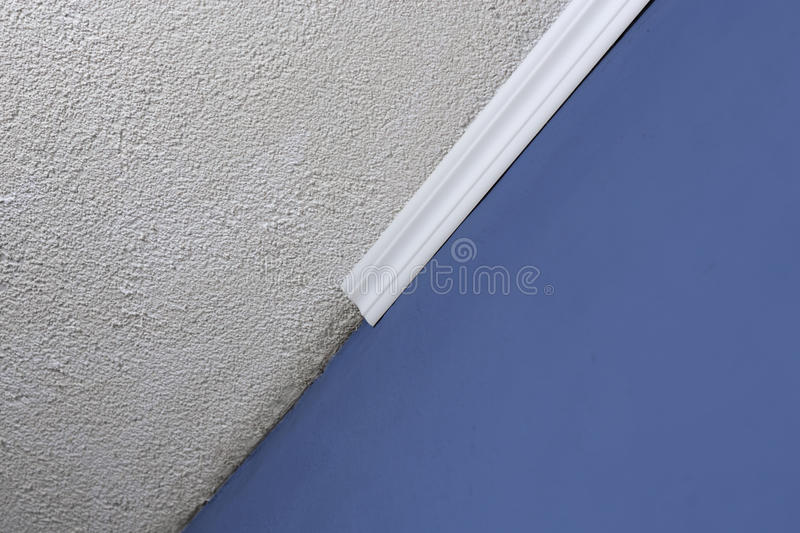 Installing crown molding on ceiling in room with painted wall. Fragment of molding, horizontal view. Home improvements stock image
