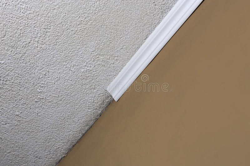 Installing crown molding on ceiling in room with painted wall. Fragment of molding, horizontal view. Home improvements stock photo