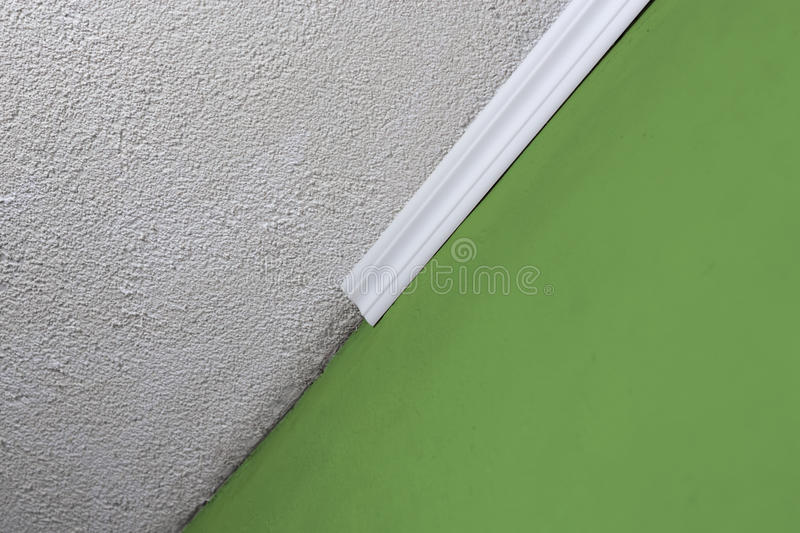 Installing crown molding on ceiling in room with painted wall. Fragment of molding, horizontal view. Home improvements royalty free stock photos
