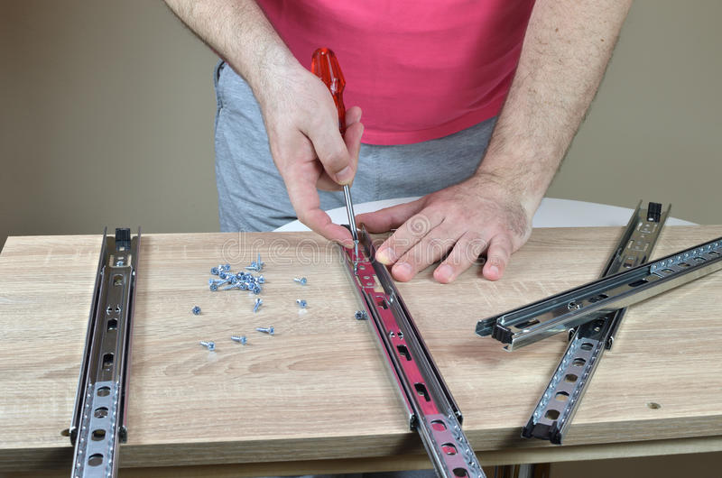Installing a Drawer Slides on a Cabinet stock photo