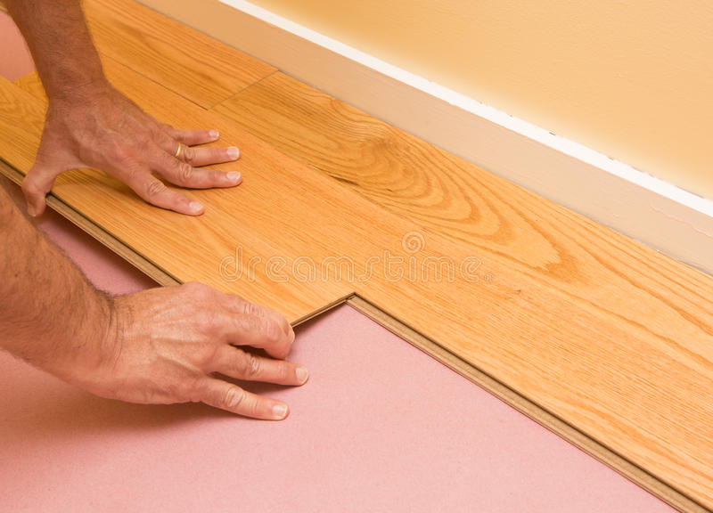 Installing Engineered Hardwood Floor. Series of shots of engineered hardwood floor being installed by a worker over pink felt paper using hand tools royalty free stock photo