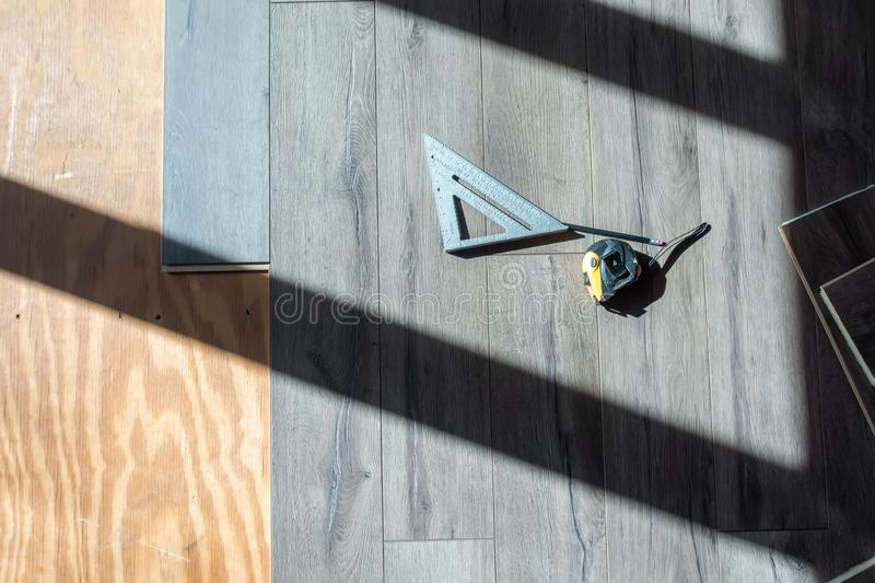 Installing engineered laminated wood flooring and tools to use royalty free stock photos