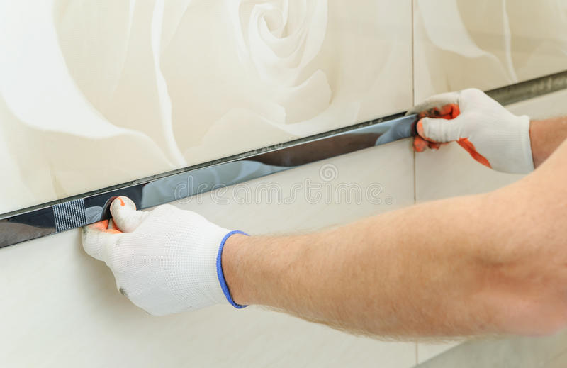 Installing the frieze on the wall. A worker putting tiles in the bathroom stock photo