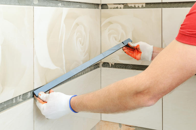 Installing the frieze on the wall. A worker putting tiles in the bathroom royalty free stock image