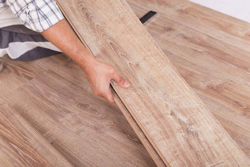Installing laminate flooring. Carpenter lining parquet boards to stock photo