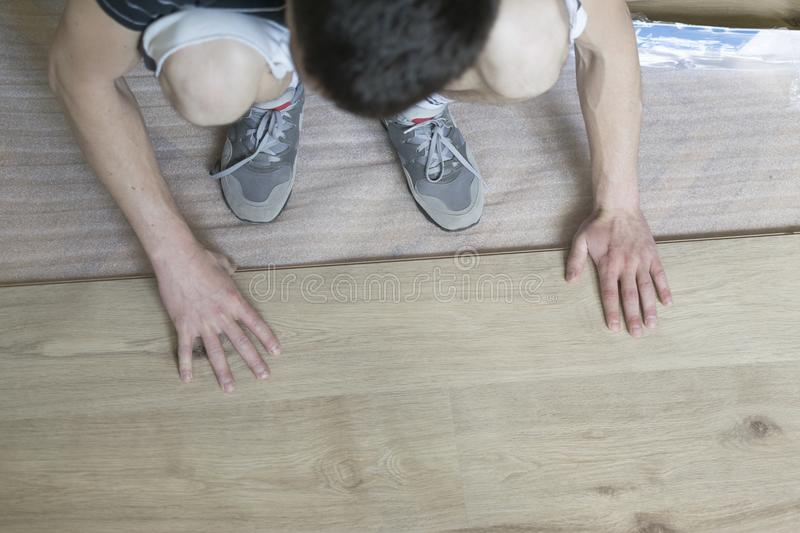 Installing laminate flooring fitting the next piece - focus on h. And stock photo