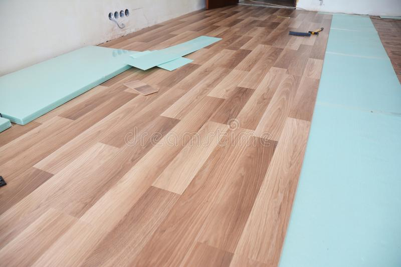 Installing wooden laminate flooring with insulation and soundproofing sheets. Installing laminate flooring with insulation and soundproofing sheets royalty free stock photo