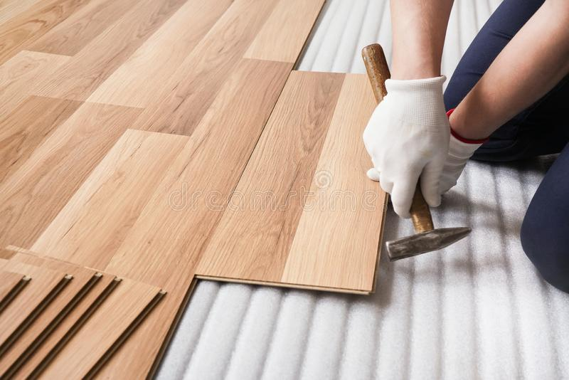 Installing laminated floor, detail on man hands fixing one tile with hammer, over white foam base layer stock image