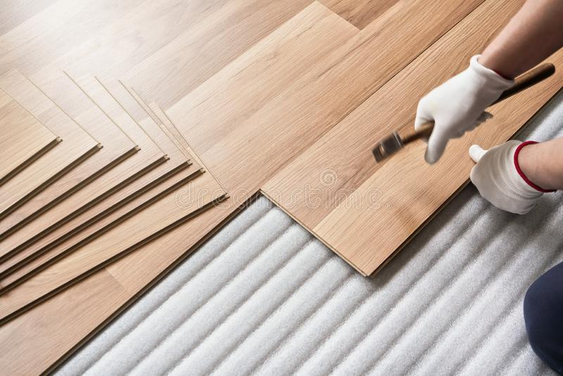 Installing laminated floor, detail on man hands holding hammer in textile gloves, over white foam base layer royalty free stock images