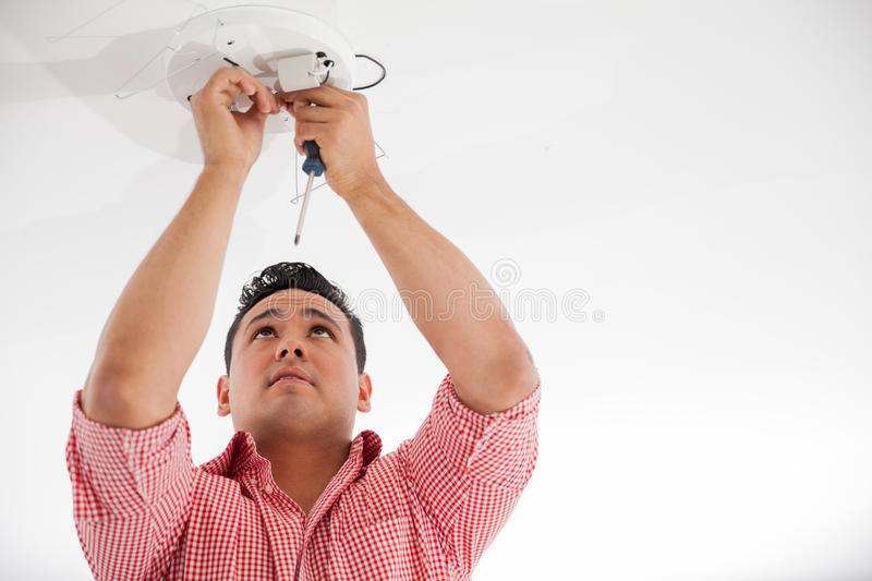 Installing a lamp on the ceiling royalty free stock photos