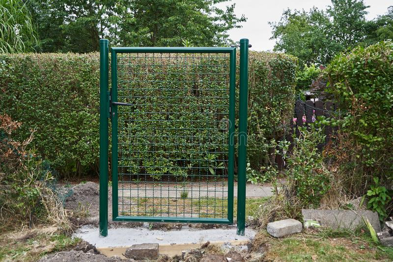 Installing a new garden gate and fence. Installing a new green mesh metal garden gate and fence around the perimeter of the property with dug up concrete and royalty free stock photo
