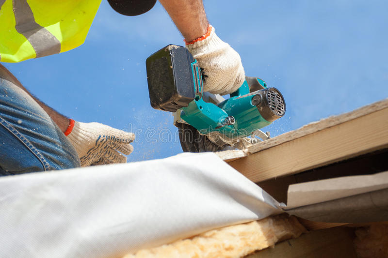 Installing a skylight. Construction Builder Worker use Circular Saw to Cut a Roof Opening for window. stock photos
