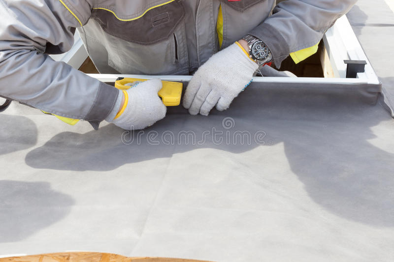 Installing Skylights in new home. Construction mason worker attach insulation material on Oriented Strand Board. stock photo