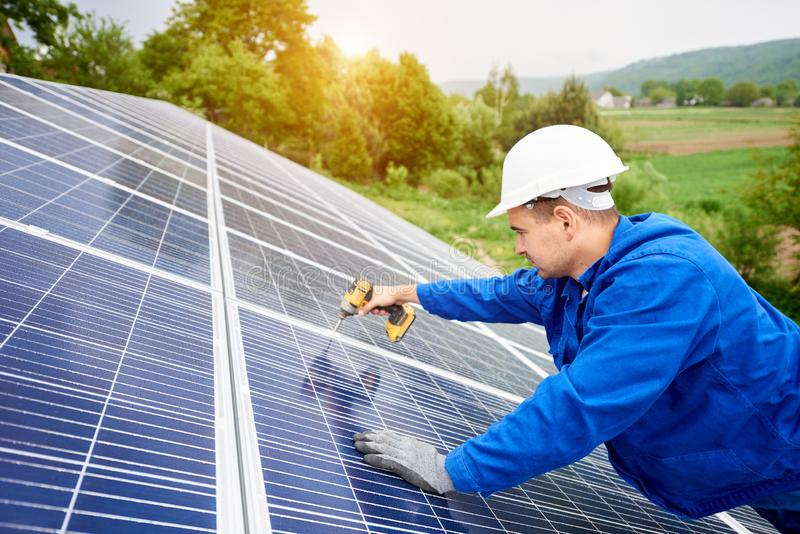 Installing of solar photo voltaic panel system. Construction worker connects photo voltaic panel to solar system using screwdriver. Professional installing and royalty free stock images