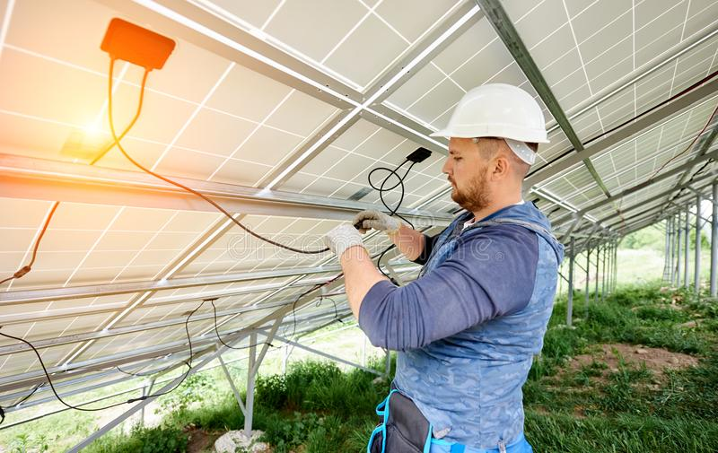 Installing of solar photo voltaic panel system. Installing and wiring of stand-alone solar photo voltaic panel system. Close-up of young electrician in hard-hat royalty free stock image