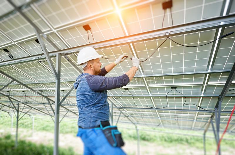 Installing of solar photo voltaic panel system. Young electrician connecting electrical cables inside the lit by sun solar modules. Installing and wiring of stock photo