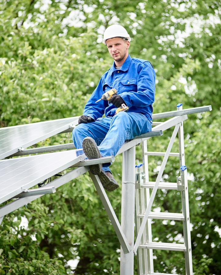 Installing of solar photo voltaic panel system. Young smiling electrician points screwdriver at camera sitting on almost finished stand-alone solar photo voltaic stock photo