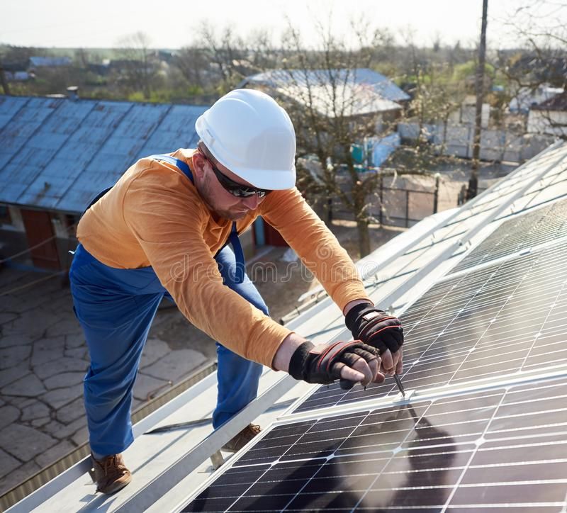 Installing solar photovoltaic panel system on roof of house stock photography