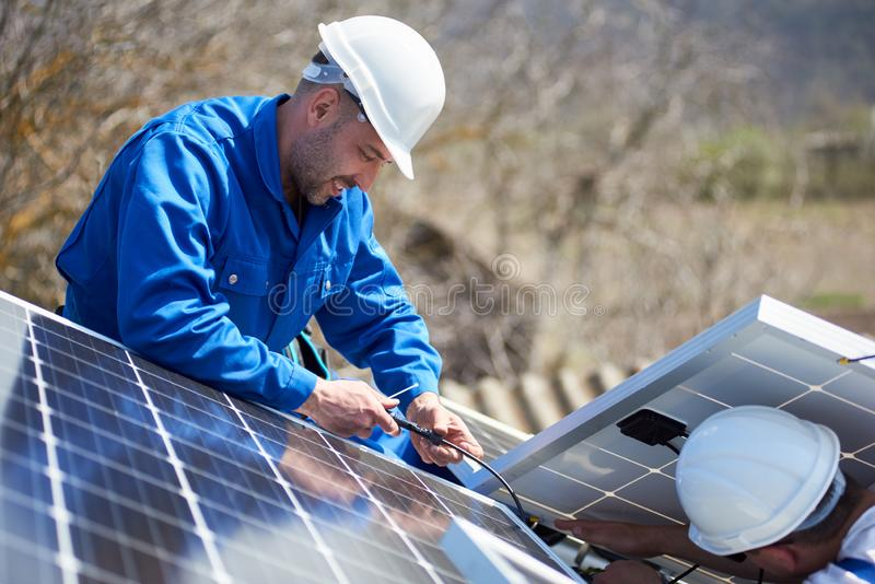Installing solar photovoltaic panel system on roof of house stock image