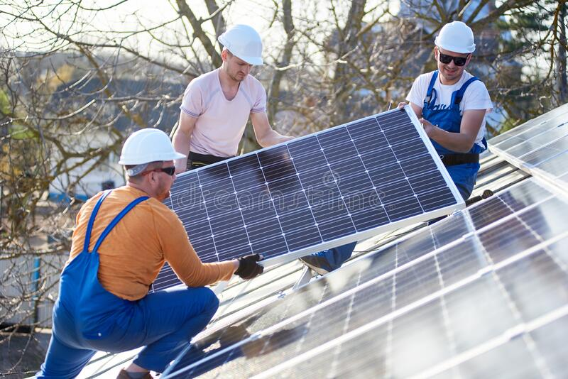 Installing solar photovoltaic panel system on roof of house stock photos