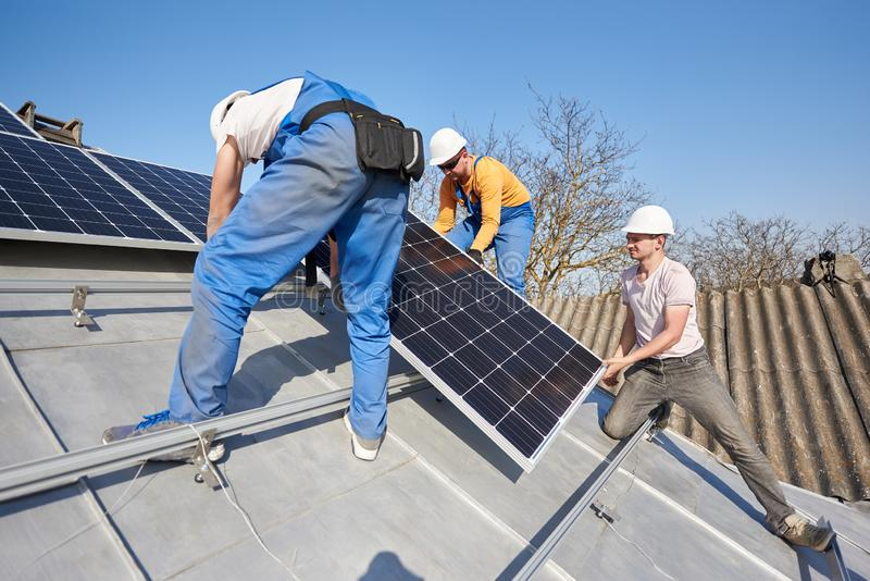 Installing solar photovoltaic panel system on roof of house royalty free stock photography