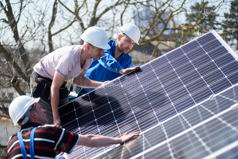 Installing solar photovoltaic panel system on roof of house. Male team workers installing solar photovoltaic panel system. Three electricians mounting blue solar stock photos