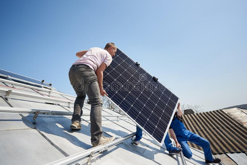 Installing solar photovoltaic panel system on roof of house. Male workers installing stand-alone solar photovoltaic panel system. Electricians lifting blue solar stock image