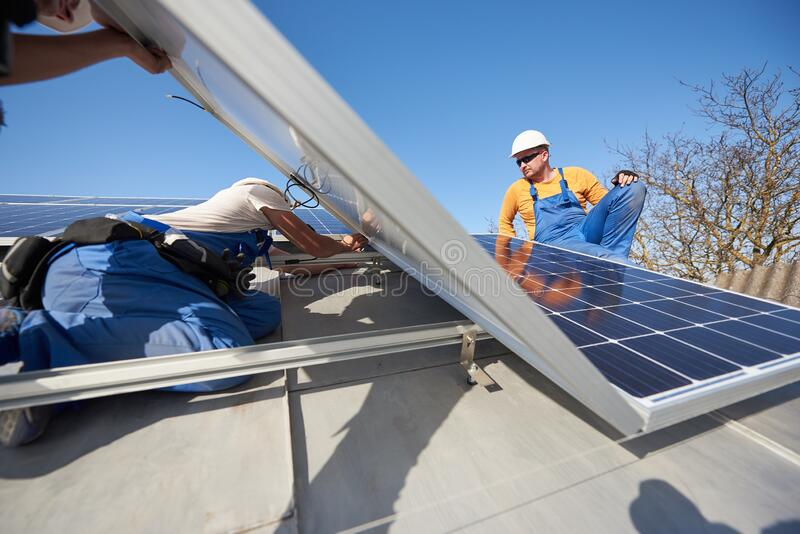 Installing solar photovoltaic panel system on roof of house royalty free stock images