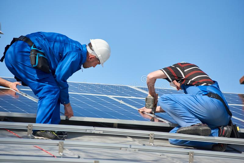 Installing solar photovoltaic panel system on roof of house stock photo