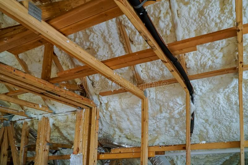 Installing thermal foam polyurea insulation under the roof wool panels and wooden planks royalty free stock photography